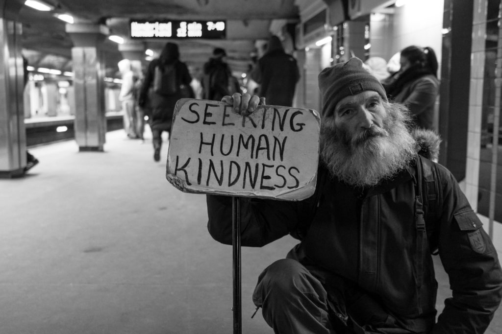 "Man carrying sign on a subway platform reading ""Seeking human kindness"""