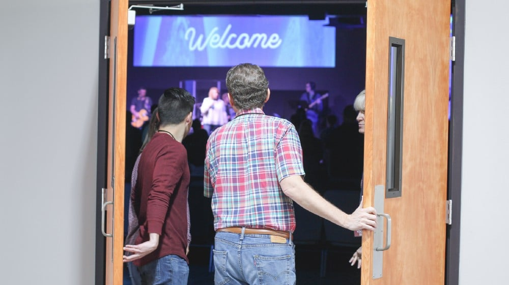 Two men, opening the doors to a church santuary.