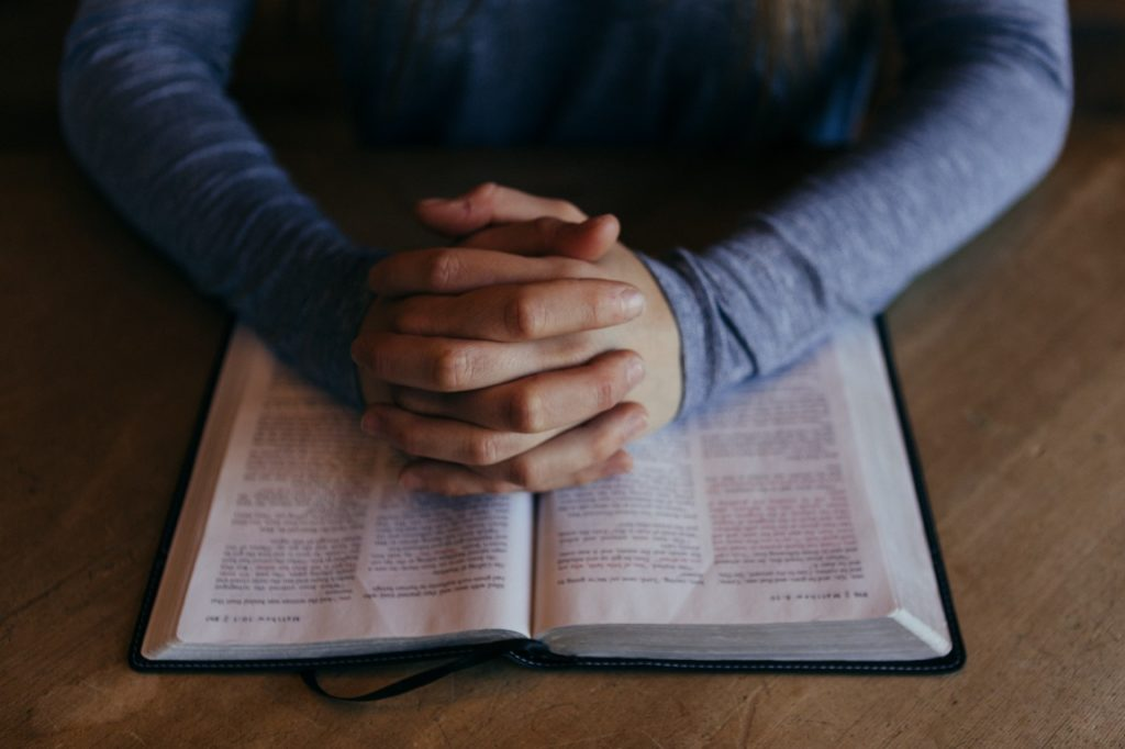 Hands folded in prayer over a Bible